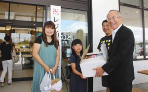 山辺芳宣市長(右)から記念品を受け取る山本さん家族=羽咋市千里浜町で