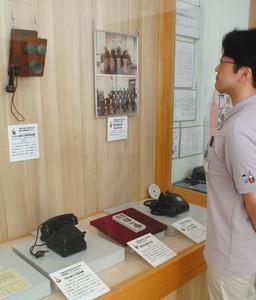 黒電話などの資料が並ぶ展示=高岡市博物館で