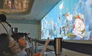 自分で描いた魚が泳ぐ様子を眺める親子=石川県七尾市ののとじま水族館で