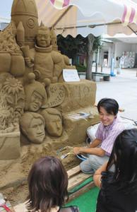 砂像について紹介しながら制作を進める古永健雄さん=金沢市の竪町広場で