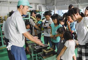 昨年の参観日の様子。工業用の機械刃物を作る「エドランド工業」で、プレスに使う金型の説明をする従業員(左)=関市下有知で