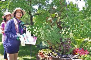 フリーダ・カーロをイメージした花壇について解説する坂本希和子さん(左から2人目)=県中央植物園で