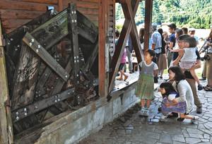 約20年ぶりに復活した水車を眺める家族連れ=白山市吉野で