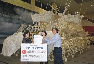 5万人目の来館者の認定書を速水館長(右)から受け取る田中さん(左)と娘の畠山さん=津市大谷町の県立美術館で