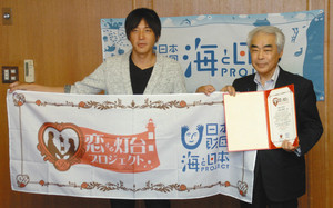 波房克典会長(左)から恋する認定書を受け取った高橋正樹市長=高岡市役所で