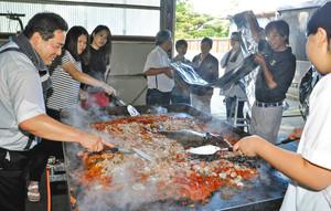 巨大パエリアを調理する参加者=白山市美川末広町で
