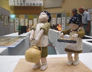 給食を運ぶ子どもの人形など、工芸品やコレクションが並ぶ総合展=高森町のくましろホールで