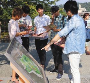 案内を頼りに問題を解く参加者=金沢城公園で