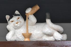 寝そべりながら酒をとっくりから杯に注ぐ木彫りネコ=南砺市井波で