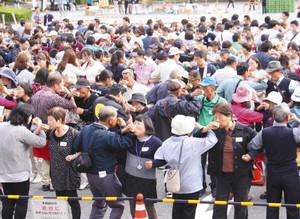 腕組みしながら、一斉に乾杯する参加者たち=養老町の養老公園で