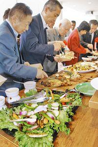 店内で地元産の野菜や果物と福地鶏の卵などを使った料理を楽しむ関係者ら=坂井市のゆりの里公園で