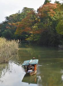 木々が赤く色づき始める中、ゆったりと進む流し舟=加賀市の旧大聖寺川で