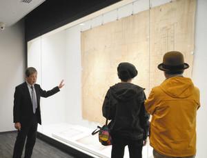 古地図の前で本多政光館長(左)から解説を受ける人たち=金沢市出羽町で