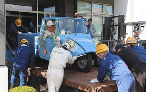 力を合わせてオート三輪を展示会場まで運び込む従業員ら=豊田市陣中町の市郷土資料館で