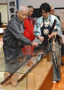 国友鉄砲研究会のメンバー(右)から、展示された鉄砲の解説を聞く来場者=長浜市木之本町のきのもと交遊館で