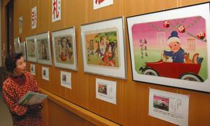 色鮮やかな引札に見入る来館者=甲賀市甲賀図書情報館で