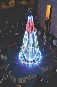 吹奏楽部の演奏が流れる中、7色に光り輝くクリスマスツリー=JR敦賀駅の交流施設「オルパーク」で