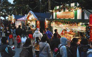 名古屋クリスマスマーケットで、本場欧州の温かい料理を求め列をつくる人たち=名古屋・栄で
