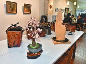 造形盆栽や彫刻などの作品と、交流を深める作家ら=高岡市駅南で