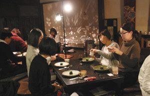 料理を前にスマートフォンで撮影する参加者=米原市醒井で