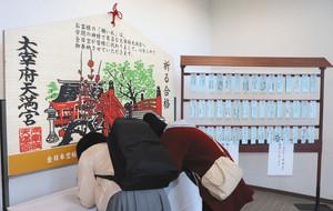 ジャンボ絵馬の下で願い事を書く人たち=富山空港で