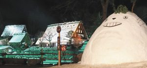 ライトアップされた合掌造り家屋とトトロの雪像=高山市上岡本町1で