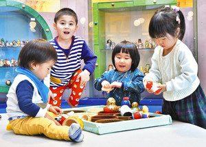 マトリョーシカが並ぶ館内で人形を手に取って遊ぶ子どもたち=県こどもみらい館で