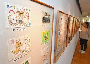 有名絵本作家らによる愛らしいイラストが描かれた年賀状=射水市大島絵本館で