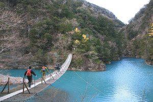 エメラルドグリーンの湖水を眺めながら、「夢の吊橋」をゆっくりと渡る人たち