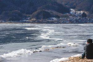 結氷した湖面に発生した亀裂。氷のせり上がりも見られる=下諏訪町赤砂崎の諏訪湖畔で