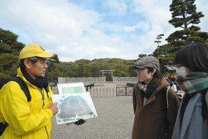拝所前で説明する観光ボランティアの柴田さん(左)=堺市の仁徳天皇陵古墳で
