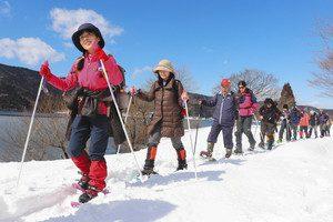 スノーシューをはいて、雪を踏み締めながら余呉湖畔を散策する参加者たち=長浜市余呉町で