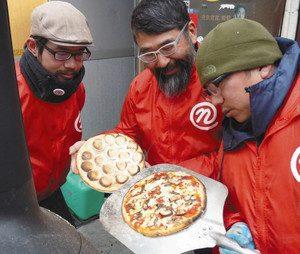 イワシを使った新作ピザの試作品(右)を焼き上げるチーム能登喰いしん坊のメンバー=穴水町で