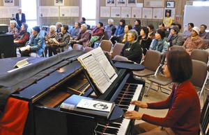中山晋平が愛用した大正時代のピアノ(手前)の伴奏で歌う人たち