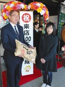 来店100万人記念のコシヒカリを受け取る大居香代子さん(右)=砺波市宮沢町で