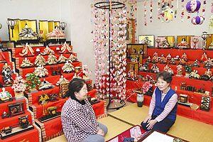 桃の実のつるしびな(中央)を作った原さん(右)ら=阿智村清内路のJA上清内路店跡地で