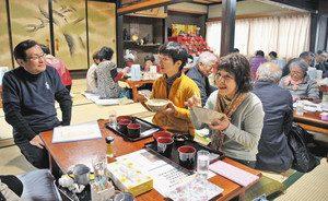 卵かけご飯などを味わう利用客をもてなす水野さん(左)=越前町のくまカフェで