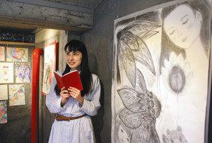 詩をつづったノートを手に新作「月光」の隣に立つ松岡理恵さん=金沢市山の上町で