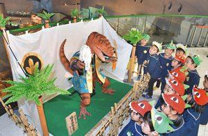 お披露目された恐竜の五月人形に興味津々の園児たち=勝山市の県立恐竜博物館で