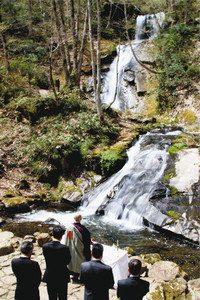 平滝の前で安全を祈願する関係者たち=高山市国府町の宇津江四十八滝で