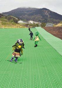 緑色のマットで作られた人工ゲレンデの滑り心地を確認するマスコットら=大野市の六呂師高原スキーパークで