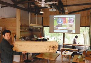 玄関に設置する手作り看板を手にするオーナーの冨士川凛太郎さん=浜松市天竜区水窪町で
