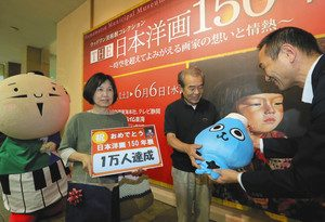 「THE日本洋画150年展」で来場者1万人目となり記念品を贈られる夫妻(中央)=浜松市中区の市美術館で