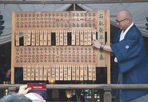 神社に練り入れる順に町名の木札が掛けられていく表=桑名市本町の春日神社で