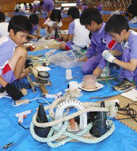 ロープや流木といった漂着ごみで冠(手前)などの作品を作る児童=氷見市窪小で