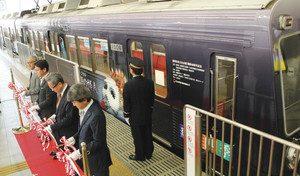 ラッピング列車の前でテープカットをする出席者=静岡市葵区で