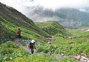 雄大な景色を背に頂を目指す登山者