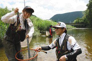 振草川で釣り上げたアユを手に笑顔の奥田さんと講師の丹羽浩和さん