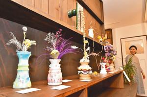 木工作家や美容師、小学生らが色を付けるなどして仕上げ、フラワーアーティスト西淵吏英さん(右奥)が花を合わせたオブジェ作品=富山市婦中町板倉で