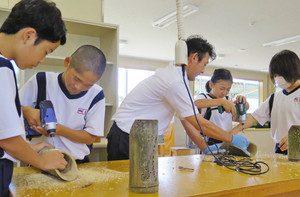 真剣な表情で竹に穴を開けていく生徒たち=湖西市岡崎で